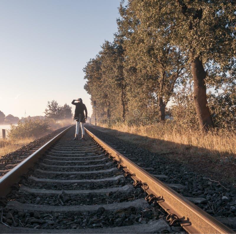 A única mulher está estando na trilha railway e está olhando no s foto de stock royalty free
