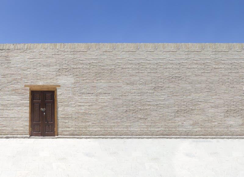 Única porta de madeira marrom na parede de tijolo Copie o espaço para o texto imagem de stock