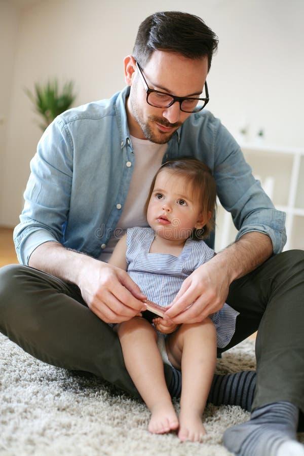 Única sagacidade do pai sua filha que usa o telefone esperto imagem de stock