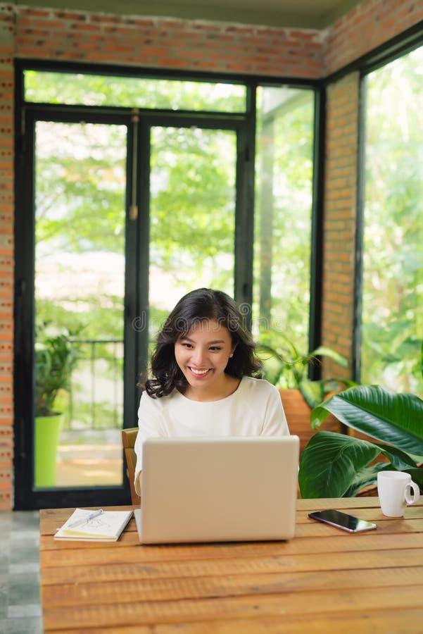 Único assento fêmea adulto sério na tabela que guarda o copo de café e que datilografa no portátil foto de stock royalty free