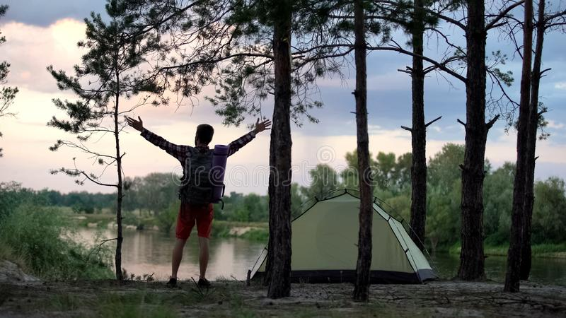 Único campista que aumenta os braços, apreciando a liberdade, amante de natureza, opinião traseira do turista imagens de stock royalty free