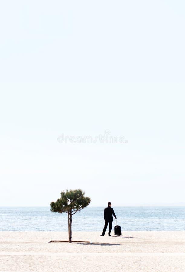 Único homem de negócio com uma bagagem que olha o mar. É triste fotos de stock royalty free