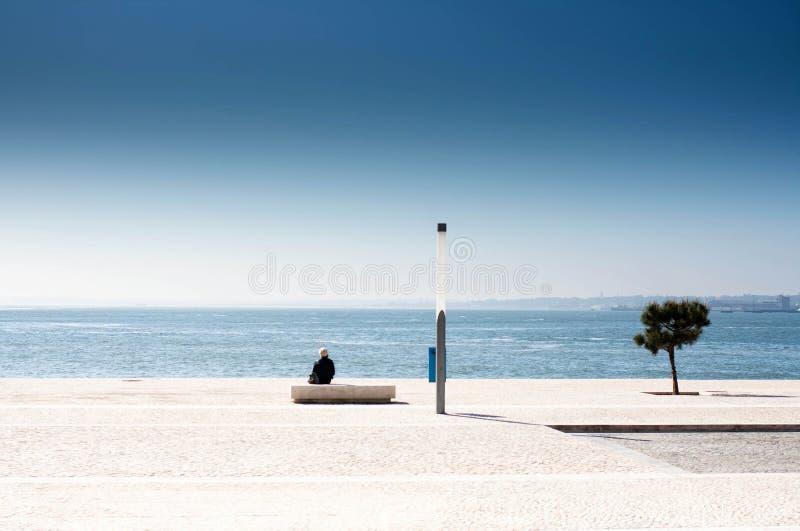 Único homem que senta-se em um banco e que olha o mar. Triste só imagens de stock