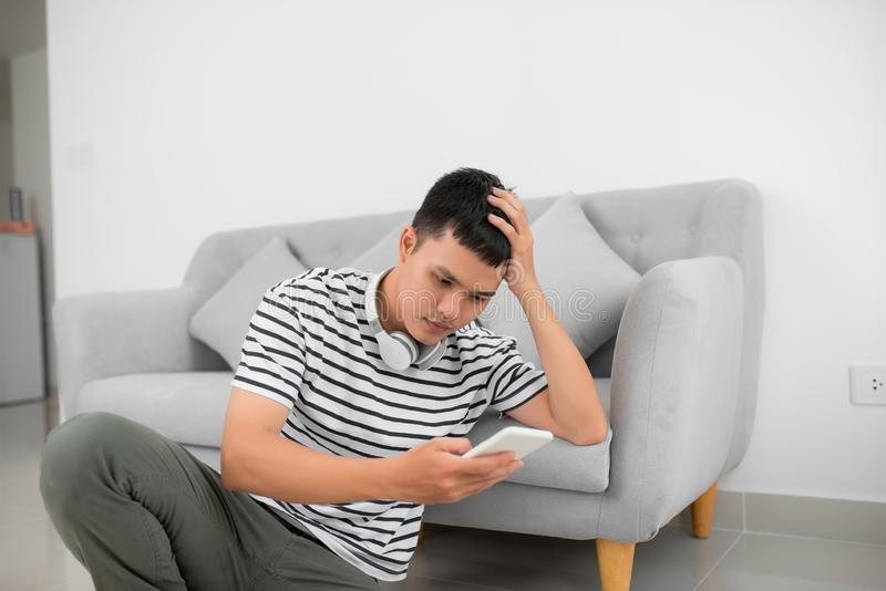 Único homem triste que verifica o telefone celular que senta-se no assoalho na sala de visitas em casa foto de stock