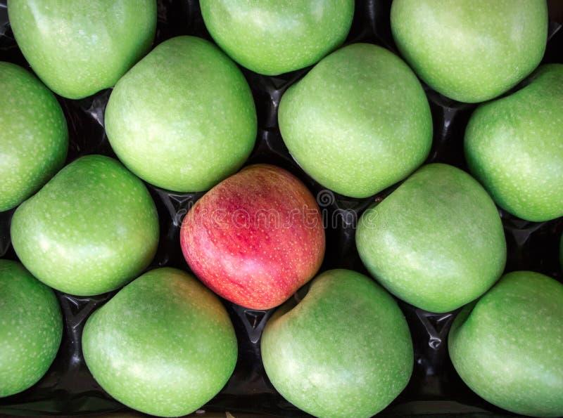 único Manzana roja entre un grupo de manzanas verdes imagenes de archivo