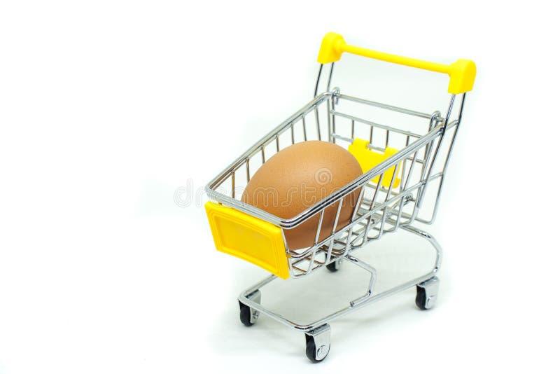 Único ovo no mini carrinho de compras ou trole amarelo do supermercado isolado no fundo branco imagem de stock