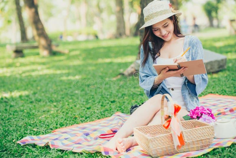Único piquenique adolescente asiático na leitura do parque fotografia de stock