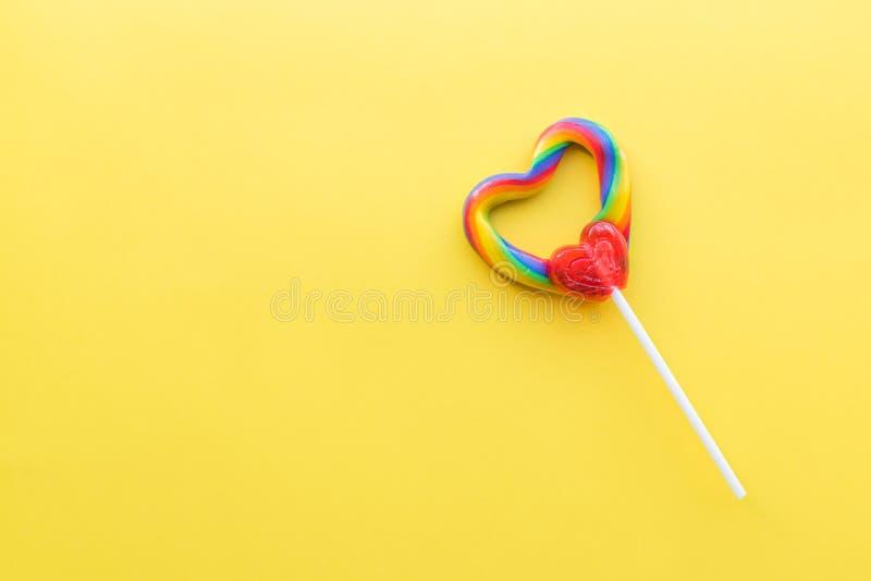 Único pirulito coração-dado forma com cores do redemoinho do arco-íris com fundo amarelo brilhante fotografia de stock