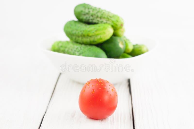 Únicos tomate e lote maduros vermelhos de pepinos frescos verdes na bacia branca no fundo de madeira fotografia de stock