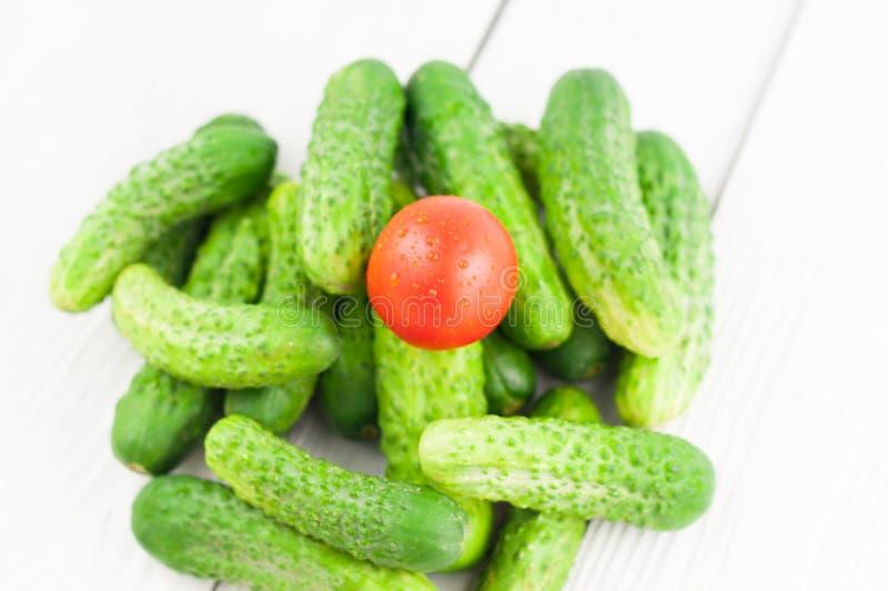 Únicos tomate e montão vermelhos de pepinos frescos verdes no fundo rústico fotos de stock royalty free