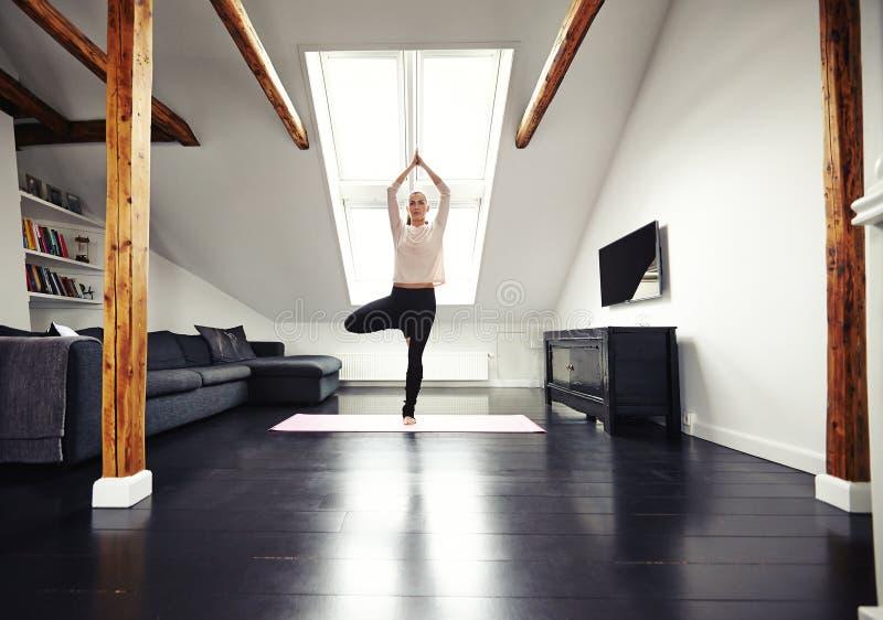 Übende Yogaübung der jungen kaukasischen Frau zu Hause lizenzfreies stockfoto