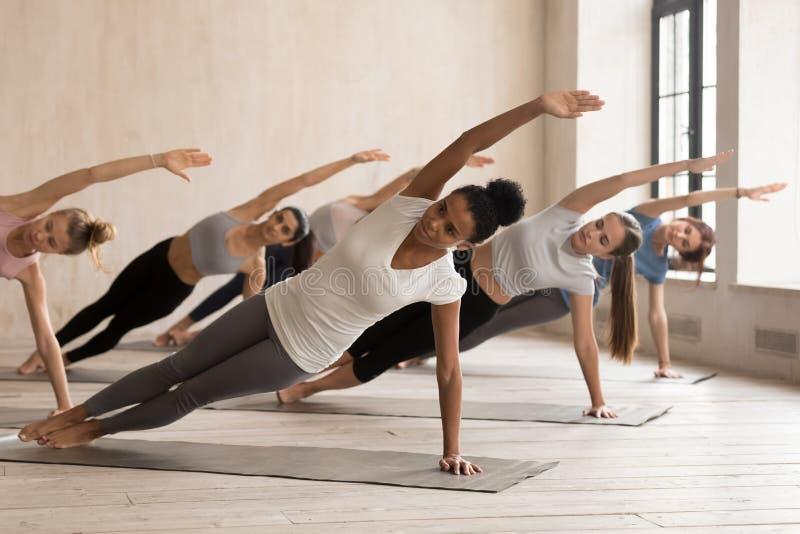 Übende Yogalektion der Frauengruppe, Seitenplankenhaltung stockbilder
