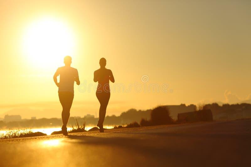 Übender Sport der Paare, der bei Sonnenuntergang auf der Straße läuft stockfotografie