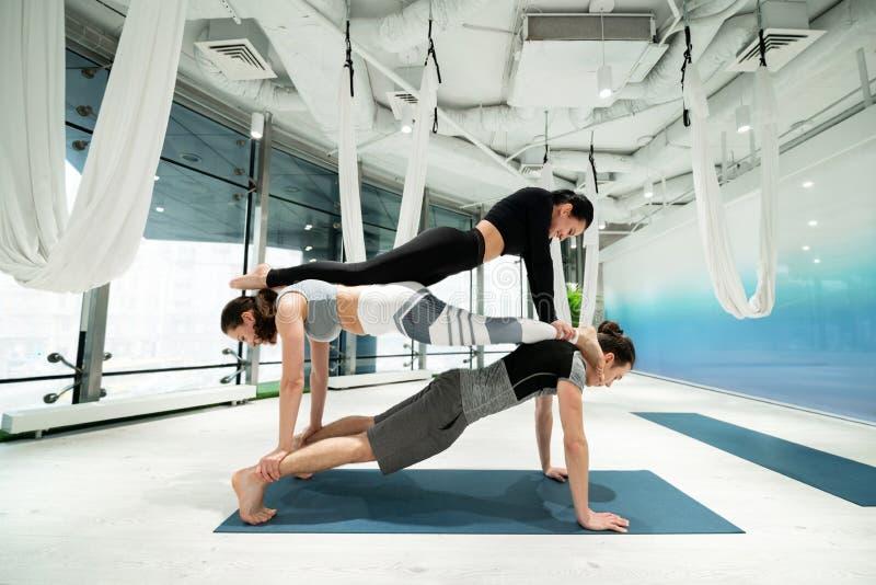 Übendes Eignungsyoga der starken Leute, das Planken auf den Rückseiten tut lizenzfreie stockfotos