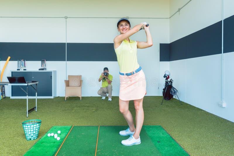 Übendes Golfschwingen der Sitzfrau während der Berufsklasse zuhause stockfoto
