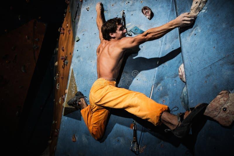 Übendes Klettern des Mannes auf einer Felsenwand lizenzfreie stockbilder