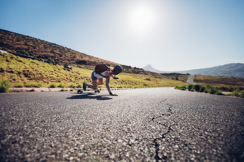 Übendes Skateboard fahren des weiblichen Schlittschuhläufers auf Landstraßen stockfotos