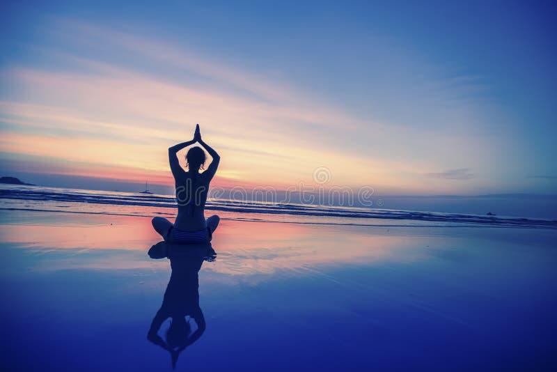 Übendes Yoga Dame auf der Ozeanseite lizenzfreie stockfotografie