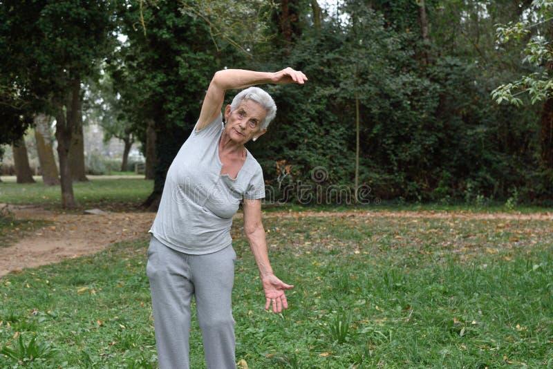 Übendes Yoga der älteren Frau draußen lizenzfreies stockfoto