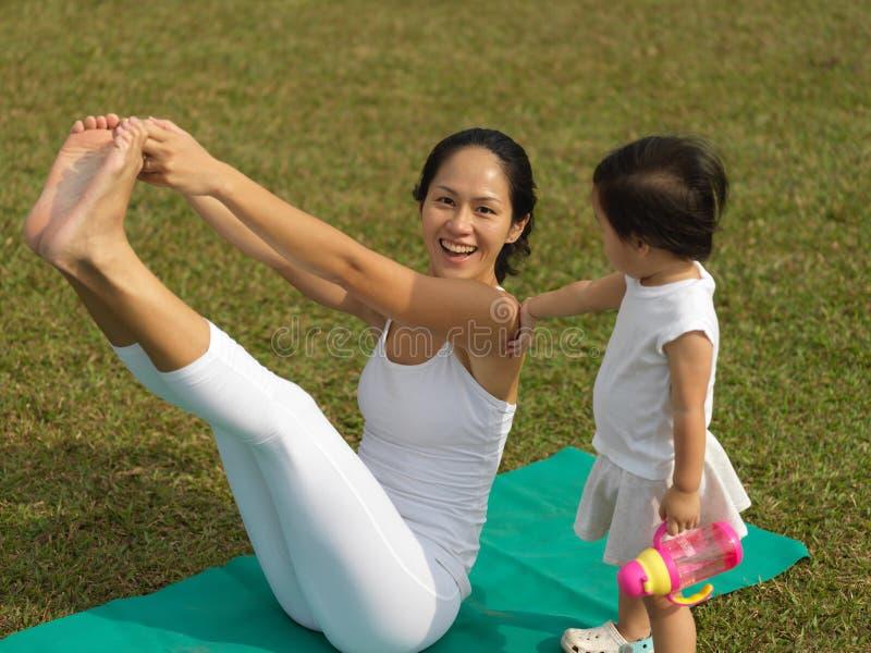 Übendes Yoga der asiatischen chinesischen Frau draußen mit jungem Baby gir lizenzfreies stockfoto