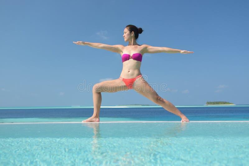 Übendes Yoga der asiatischen chinesischen Frau durch das Meer lizenzfreie stockbilder