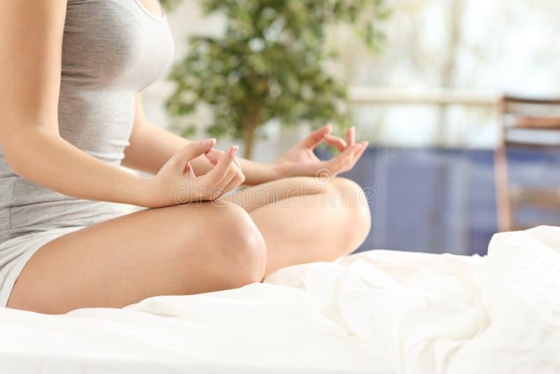Übendes Yoga der Frau auf dem Bett lizenzfreie stockbilder