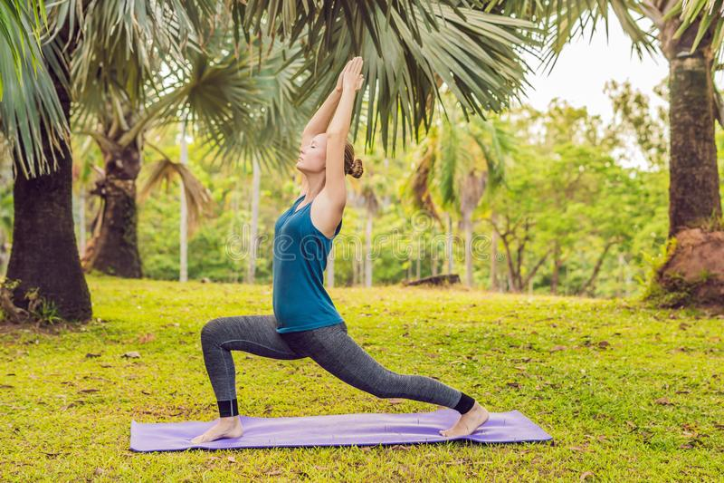 Übendes Yoga der Frau in einem tropischen Park lizenzfreie stockfotos