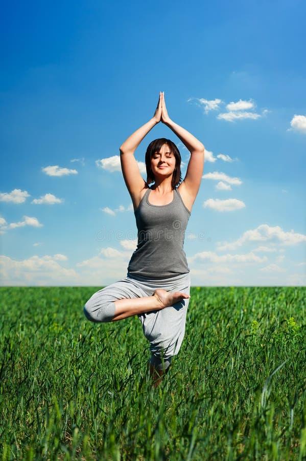 Übendes Yoga der Frau am Feld lizenzfreie stockfotos