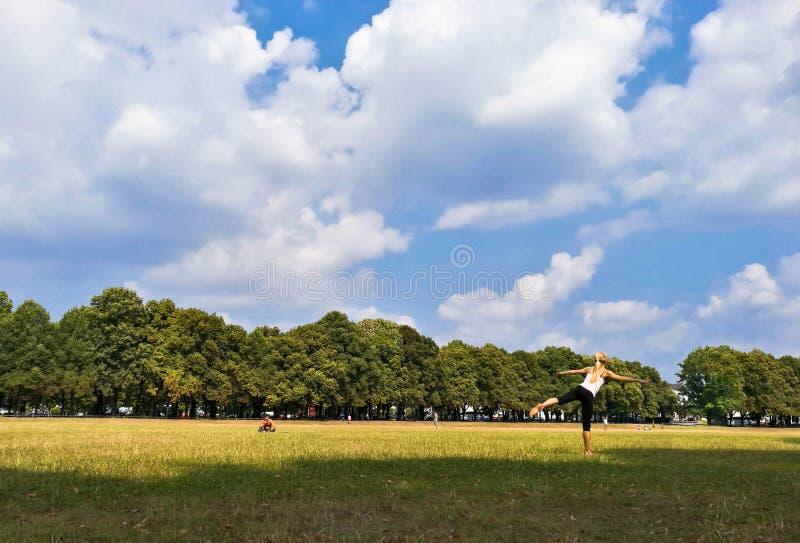 übendes Yoga der Frau im Freien im Park an einem sonnigen Tag lizenzfreie stockbilder