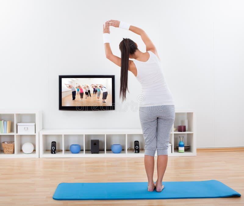 Übendes Yoga der Frau zu Hause stockbilder