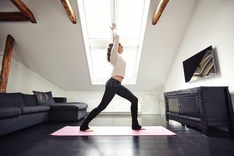 Übendes Yoga der geeigneten Frau im Wohnzimmer lizenzfreies stockfoto