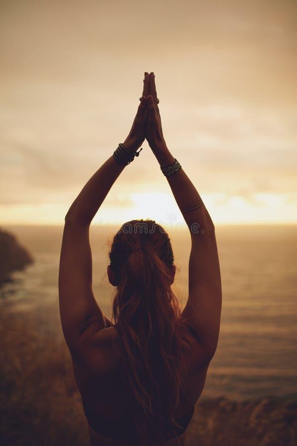 Übendes Yoga der gesunden Frau bei Sonnenuntergang stockbild