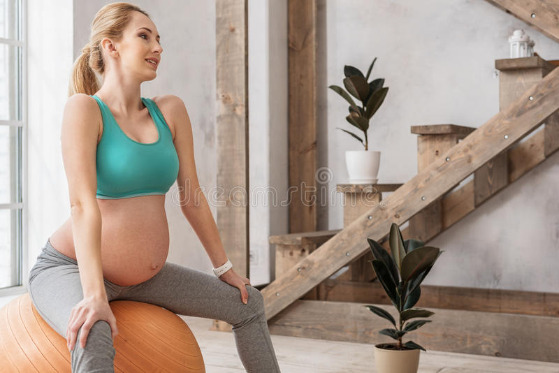 Übendes Yoga der gesunden zukünftigen Mutter stockfoto
