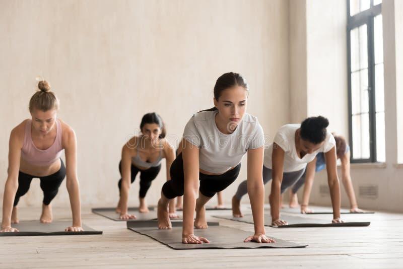 Übendes Yoga der Gruppe von Personen, drückt ups, oder Presse ups stockfotografie