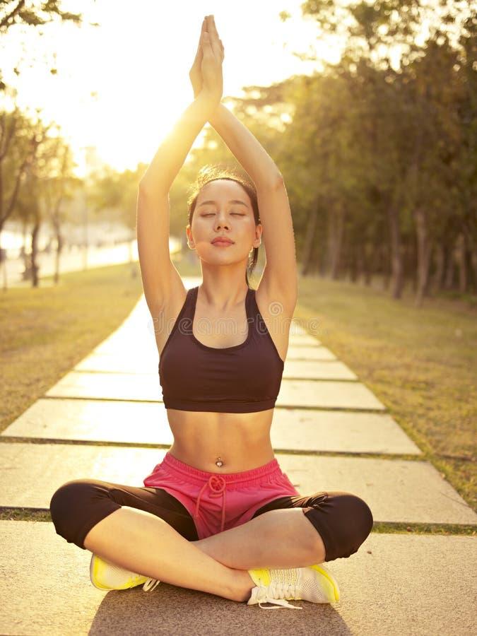 Übendes Yoga der jungen asiatischen Frau draußen bei Sonnenuntergang stockfoto