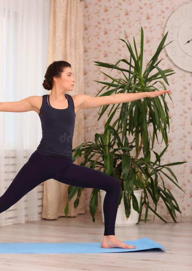 Übendes Yoga der jungen attraktiven Frau, nachdem es aufgewacht ist und in Krieger zwei gestanden, trainiert, Haltung Virabhadras stockfoto