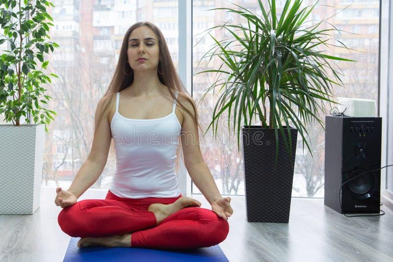 Übendes Yoga der jungen attraktiven Frau, sitzend in Übung Ardha Padmasana, halbe Lotus-Haltung und arbeiten, tragendes weißes T- stockbild