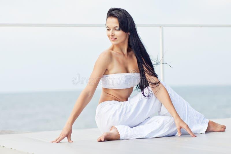 Übendes Yoga der jungen Brunettefrau durch das Meer stockfotos