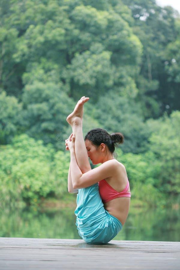 Übendes Yoga der jungen chinesischen Frau im Freien stockbild