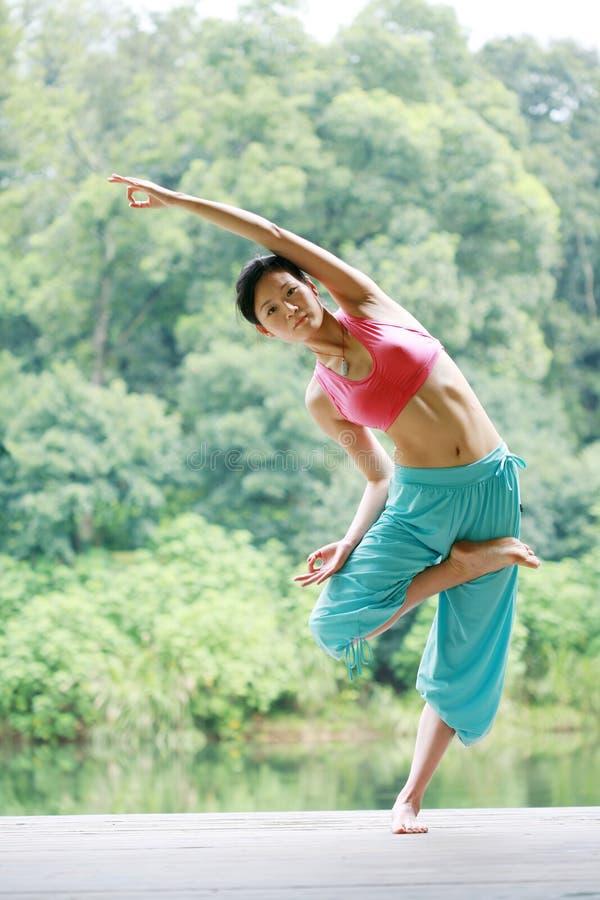 Übendes Yoga der jungen chinesischen Frau im Freien lizenzfreie stockfotos