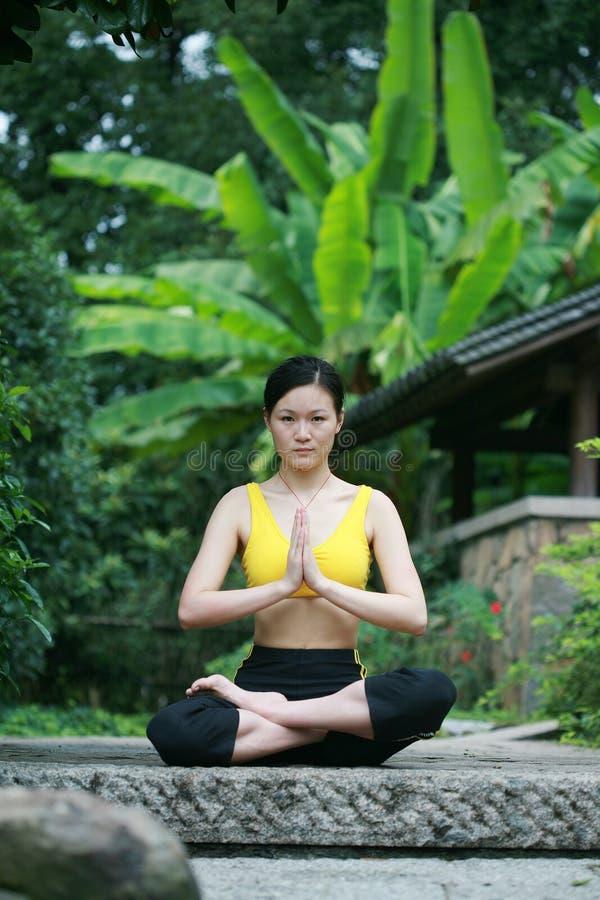Übendes Yoga der jungen chinesischen Frau im Freien stockfotos