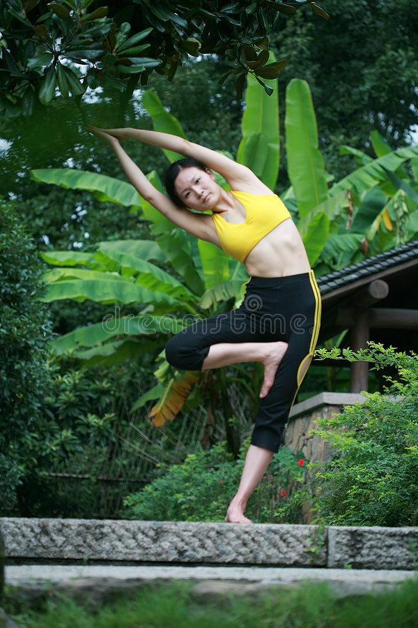 Übendes Yoga der jungen chinesischen Frau im Freien lizenzfreies stockfoto
