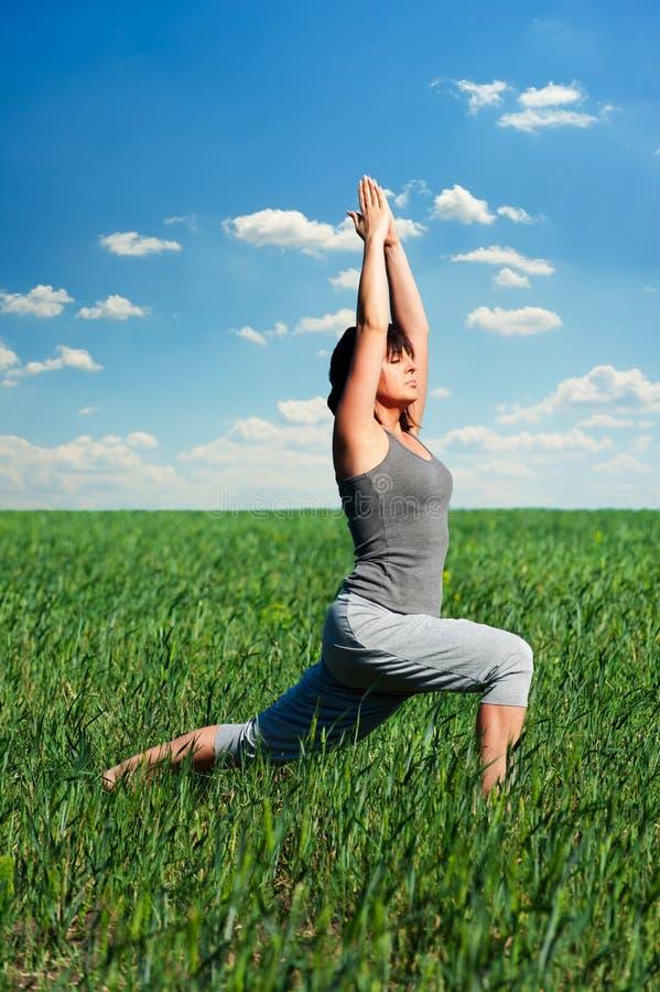 Übendes Yoga der jungen Frau lizenzfreies stockfoto