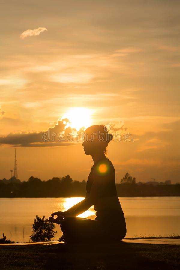 Übendes Yoga der jungen Frau auf dem Park bei Sonnenuntergang am Abend, Schattenbild stockfoto