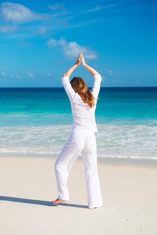 Übendes Yoga der jungen Frau auf dem Strand stockbild
