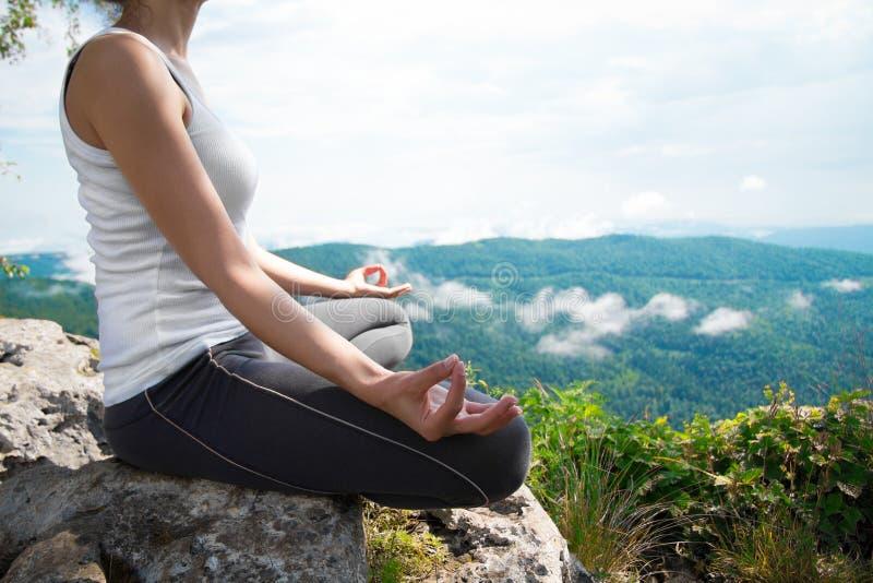Übendes Yoga der jungen Frau auf eine Gebirgsoberseite lizenzfreie stockbilder