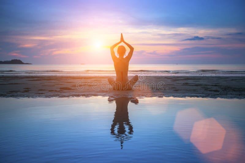 Übendes Yoga der jungen Frau des Schattenbildes auf Strand lizenzfreie stockbilder
