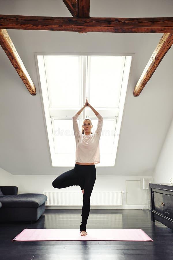 Übendes Yoga der jungen Frau im Wohnzimmer lizenzfreie stockfotos