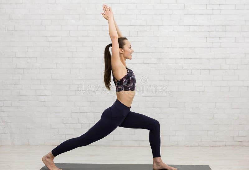 Übendes Yoga der jungen Frau, stehend in der Kriegershaltung, Seitenansicht stockfotos