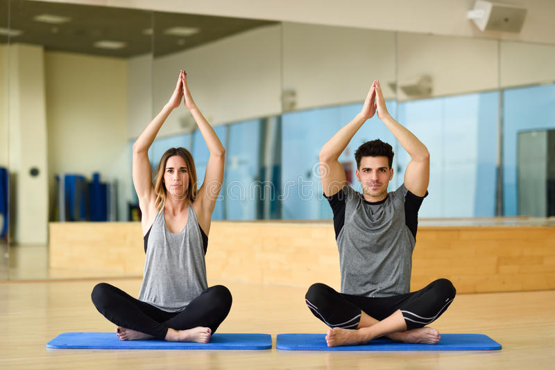 Übendes Yoga der jungen Frau und des Mannes zuhause stockfotos